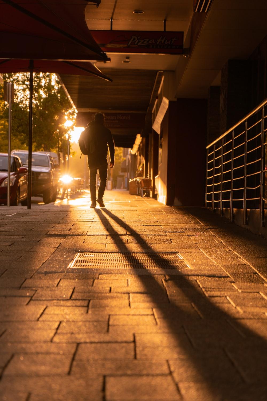 man walking on sidewalk during night time
