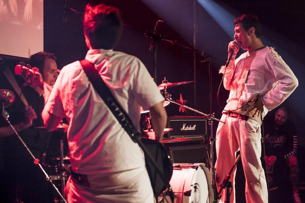 man in white dress shirt singing on stage
