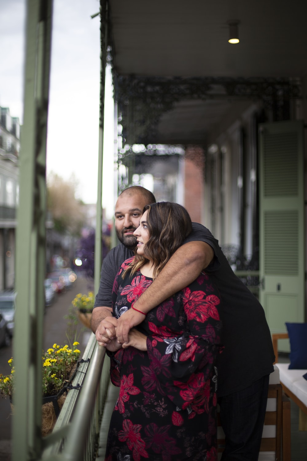 woman in black and pink floral dress hugging man in black t-shirt