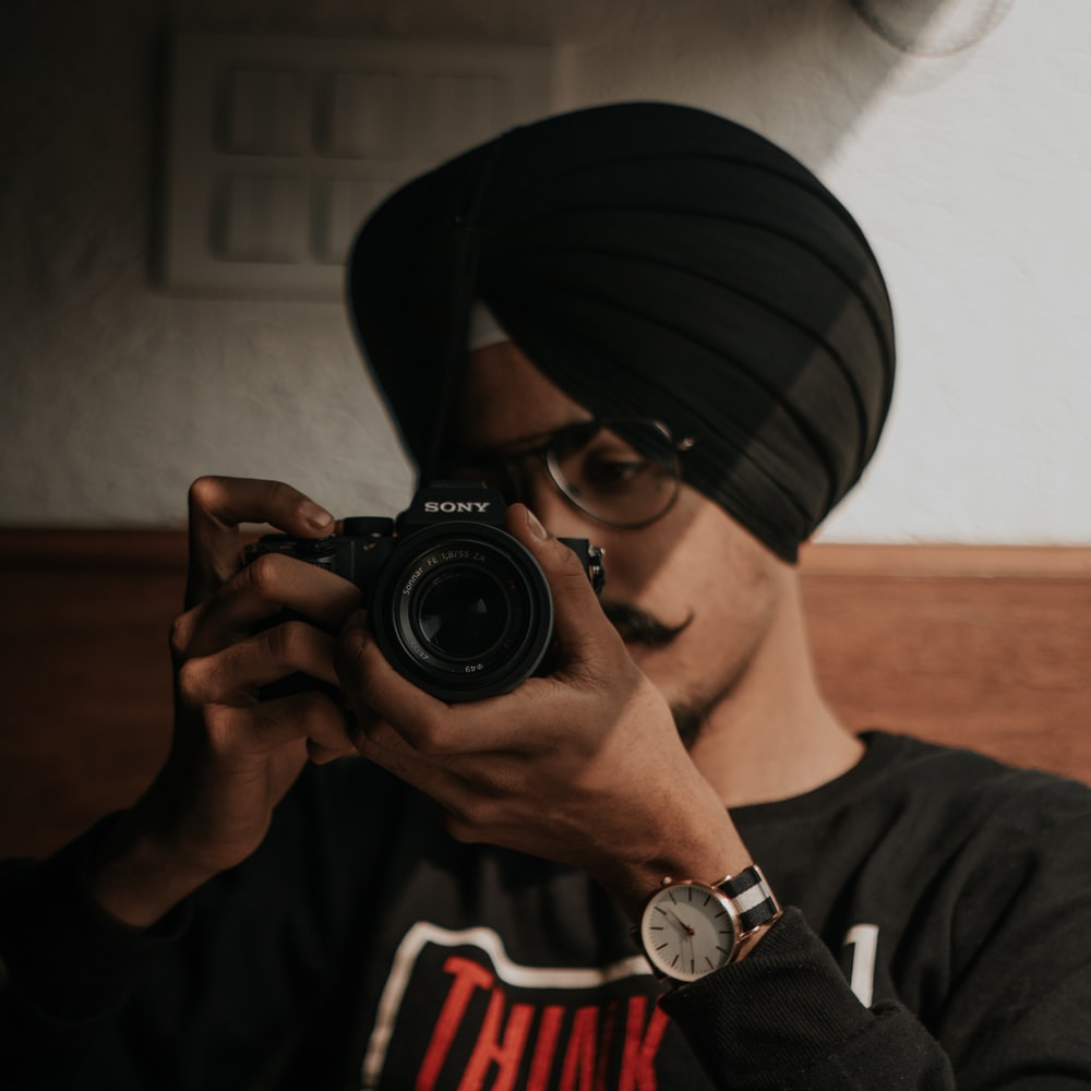 man in black and white fitted cap holding black nikon dslr camera