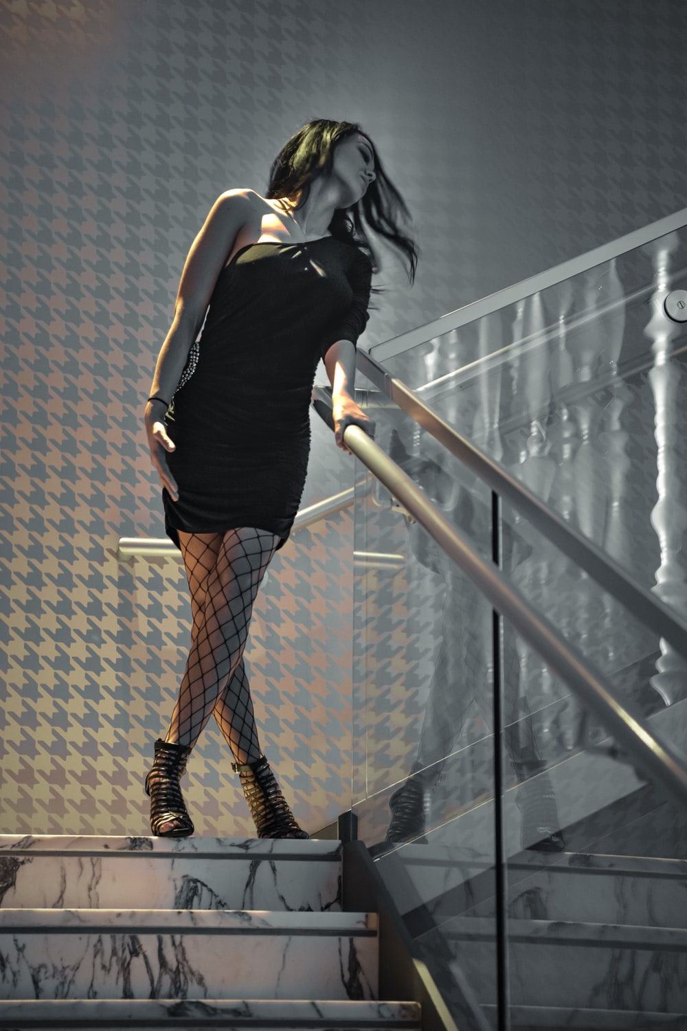 woman in black sleeveless shirt and brown skirt standing on staircase
