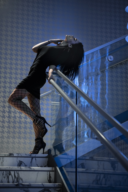 woman in black long sleeve shirt and black pants sitting on white metal railings