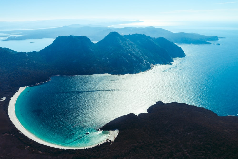 blue sea near mountain during daytime