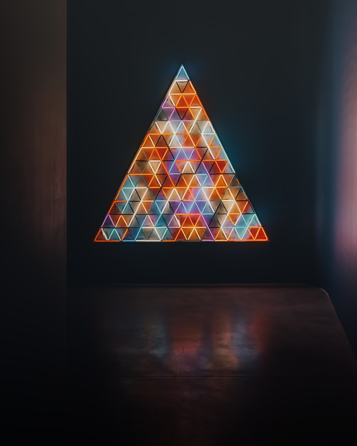 A photo of an art installation that is a triangle full of smaller triangles, each one lit up with a different colour's light. It is beautiful!