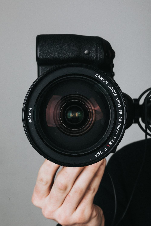 black nikon dslr camera on persons hand