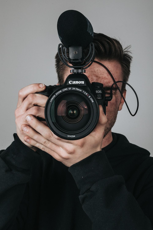 man in black long sleeve shirt holding black nikon dslr camera