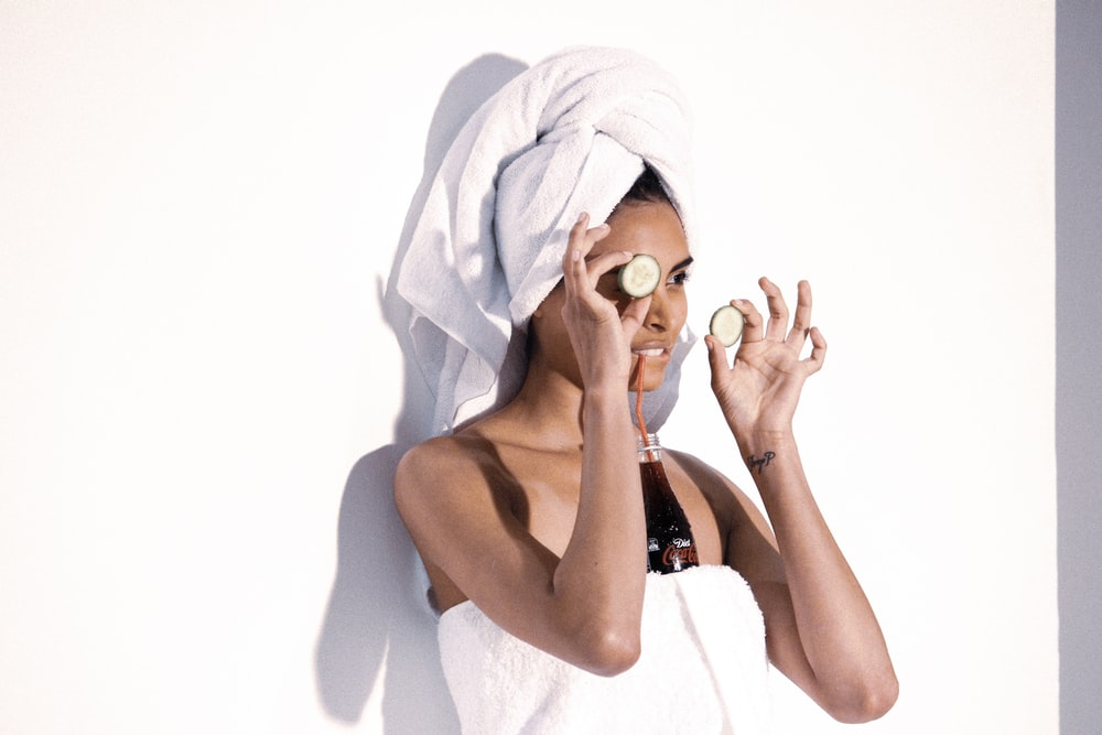 woman in white towel covering her face with blue towel