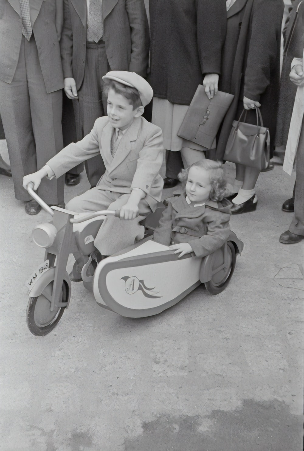 grayscale photo of children riding on trike
