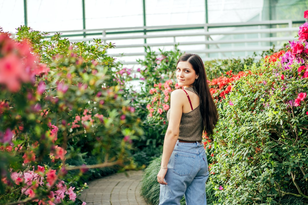Woman In Brown Tank Top and Blue Denim Jeans Standing On Pathway - unsplash