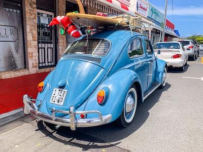 blue volkswagen beetle parked beside brown wooden post during daytime