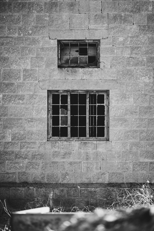 grayscale photo of window on brick wall