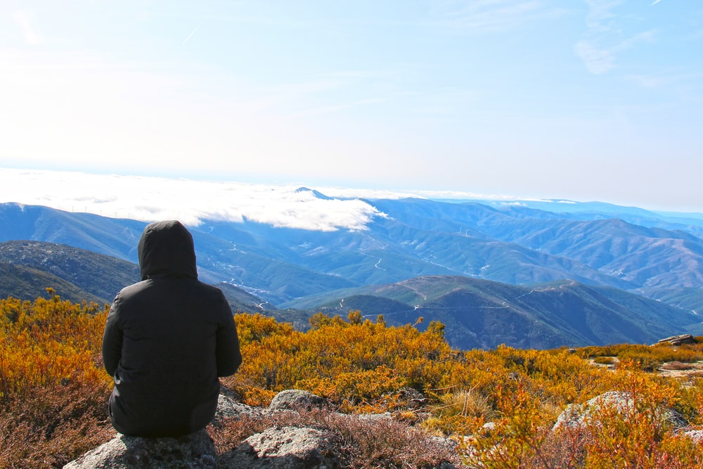 person in black jacket sitting on rock near mountains during daytime