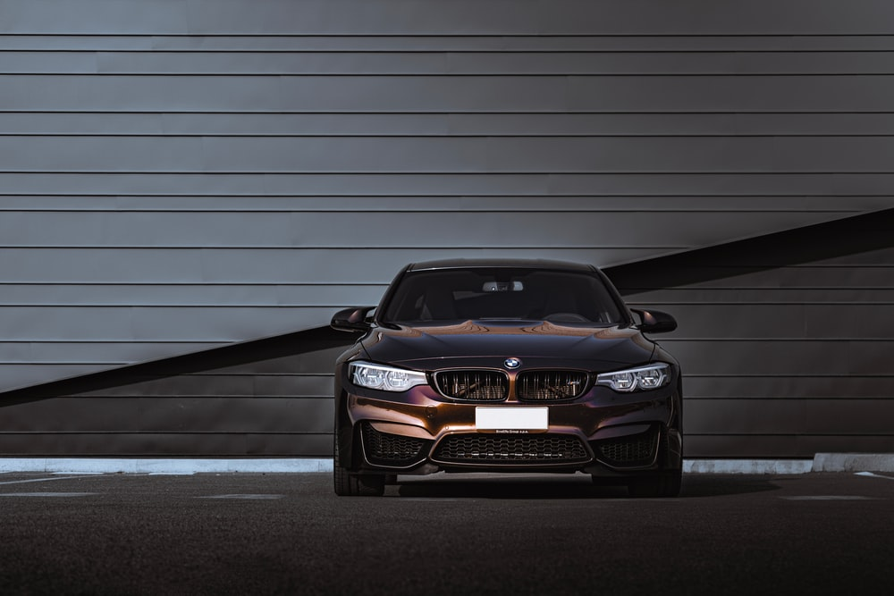 black bmw m 3 parked in front of white garage door