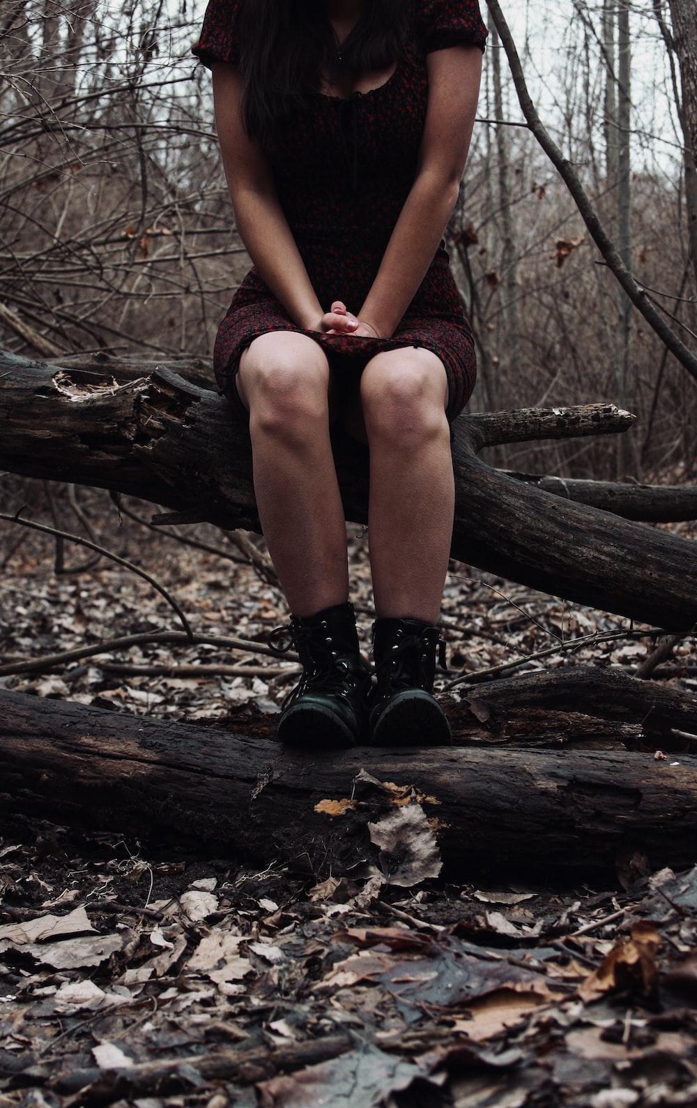 woman in black stockings sitting on brown tree log