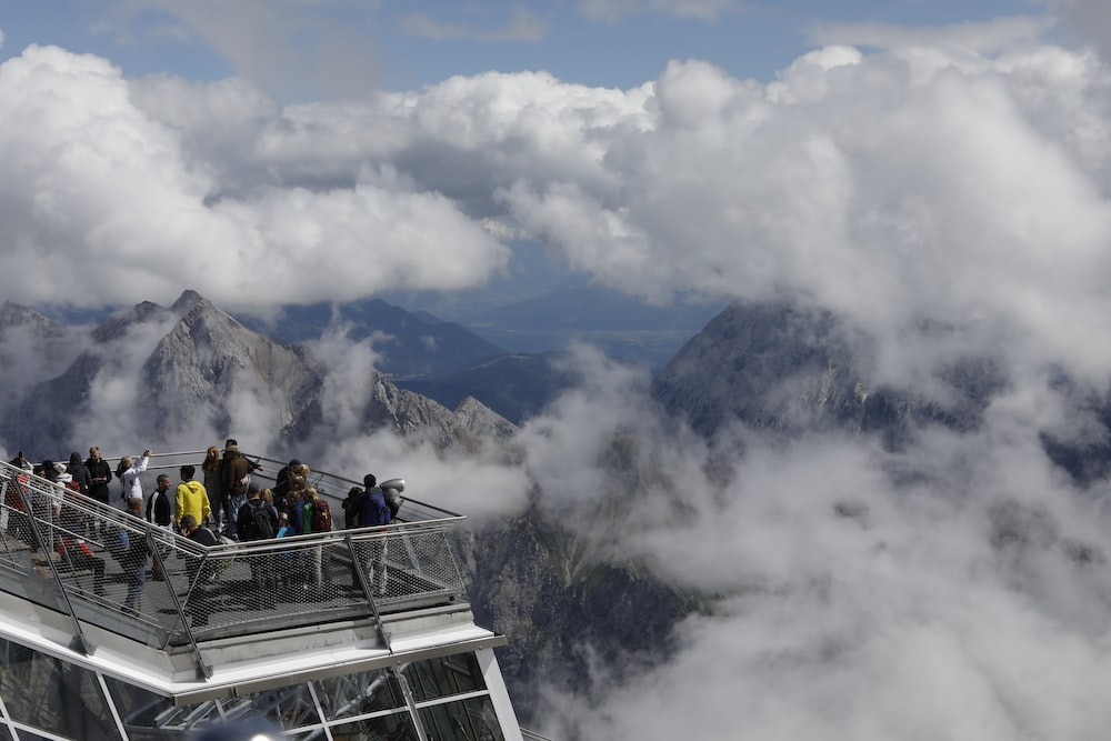 people riding on cable car under white clouds during daytime