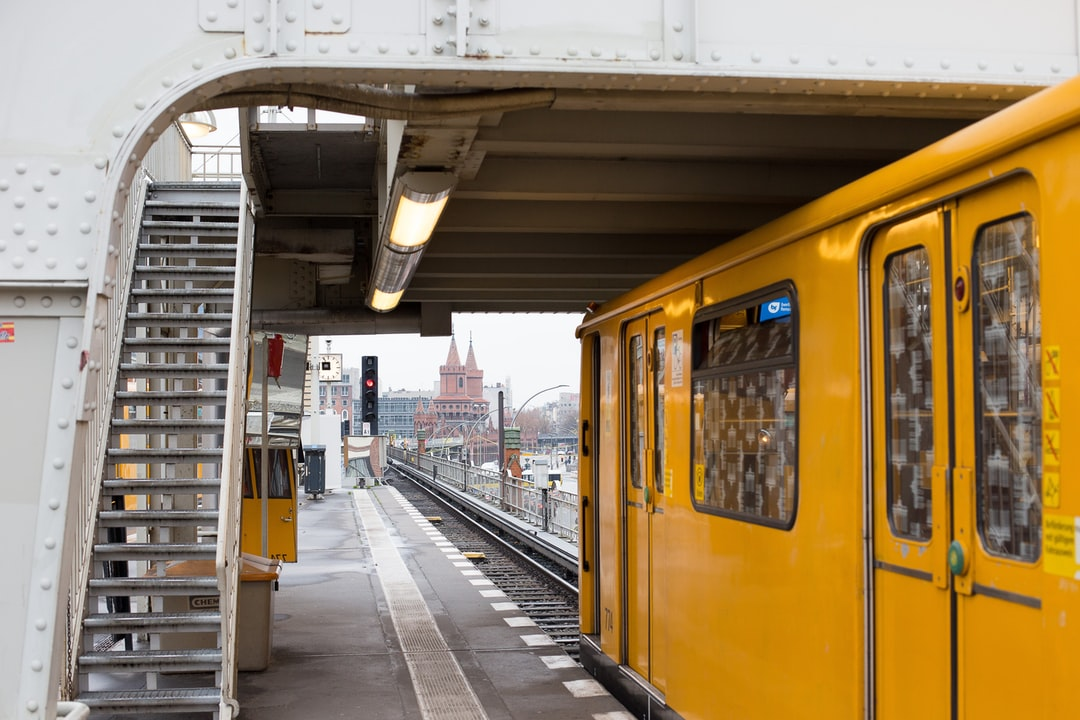 The yellow train at the station. The weather is cloudy. The wagon is yellow. The lights are turned on without any necessity. There is a small castle in the background. The photo is framed by a white metal bridge with a camera on it.  There are stairs on the left side of the picture.
