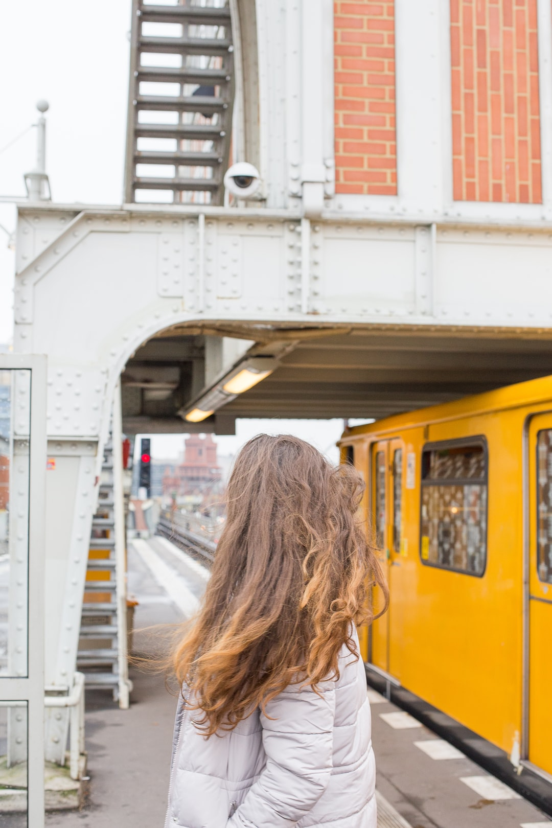 Warschauer Strasse, a woman at the station. The woman is young with long curly hair. She is turned back and is looking to the light. Her hair is following the wind. There is a yellow train on the right side of the photo. The photo is framed by the white metal bridge. There are stairs on the left side of the photo.