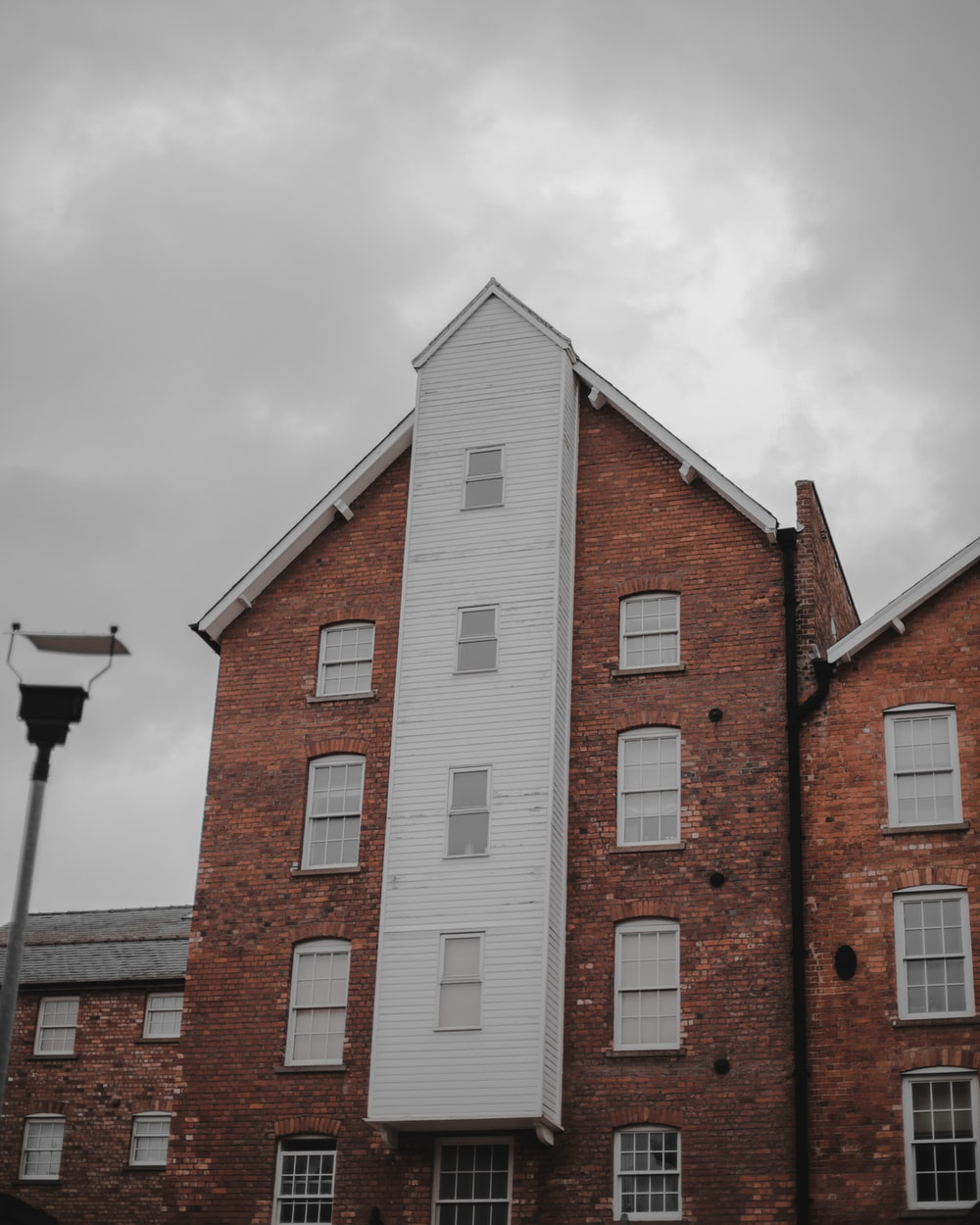 brown and white brick building under white clouds during daytime