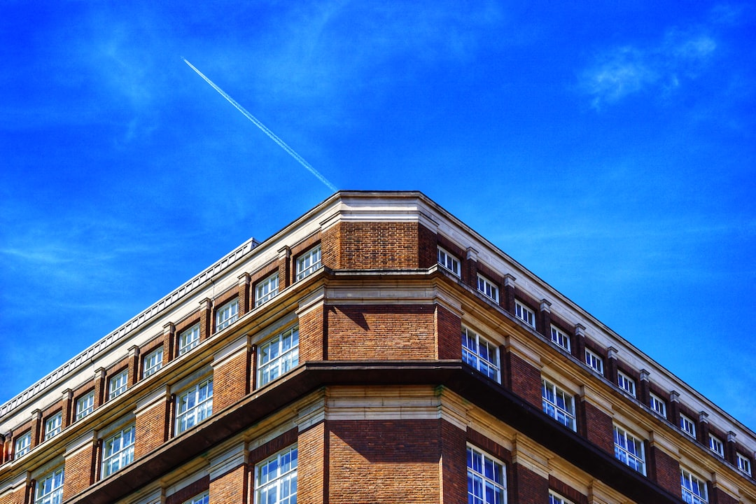 A symetric building, blue sky and airplane trail.
