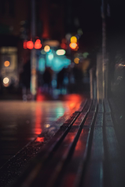 black wooden bench on sidewalk during night time