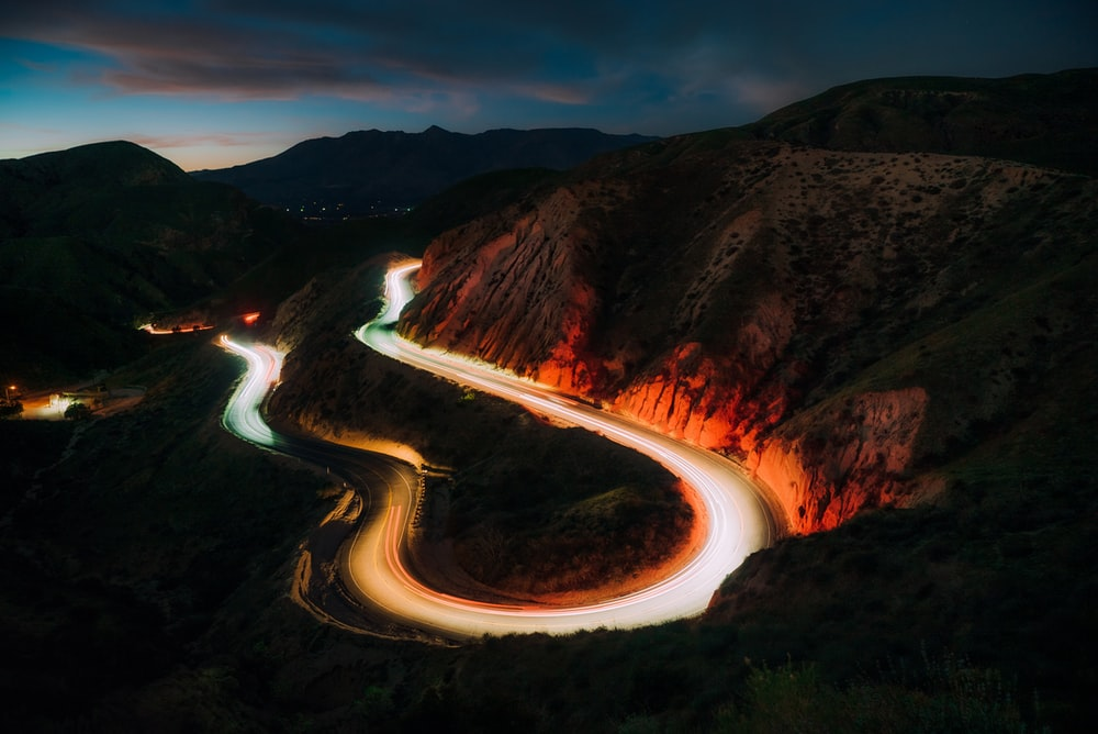 time lapse photography of river between brown mountains during night time