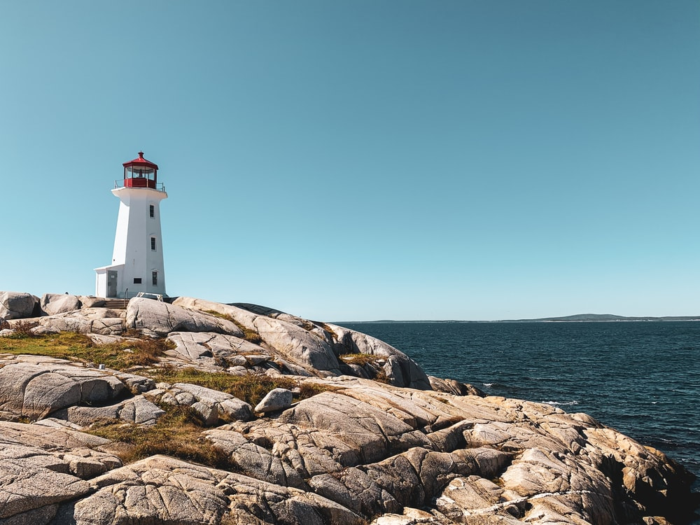 white and red lighthouse on brown rocky shore under blue sky during daytime