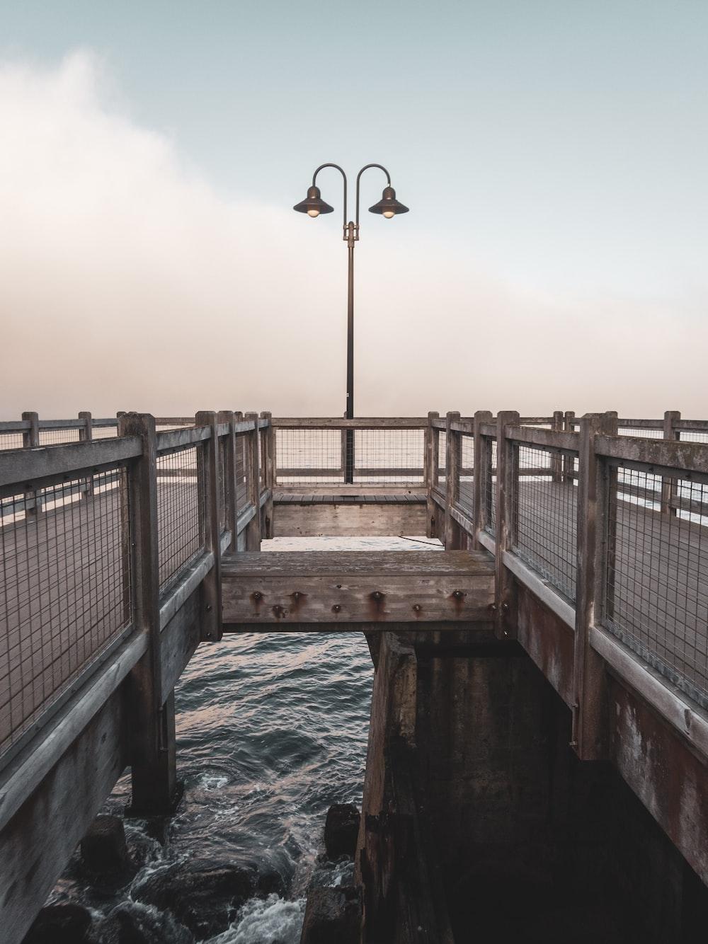 brown wooden bridge over water during daytime