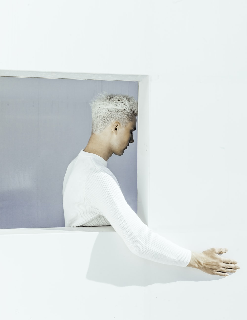 man in white sweater leaning on white wall