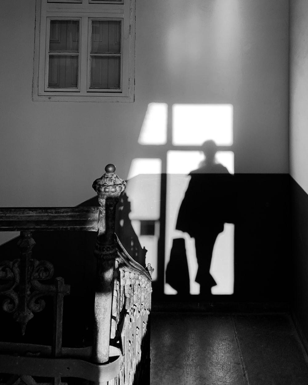 grayscale photo of woman in dress standing near window