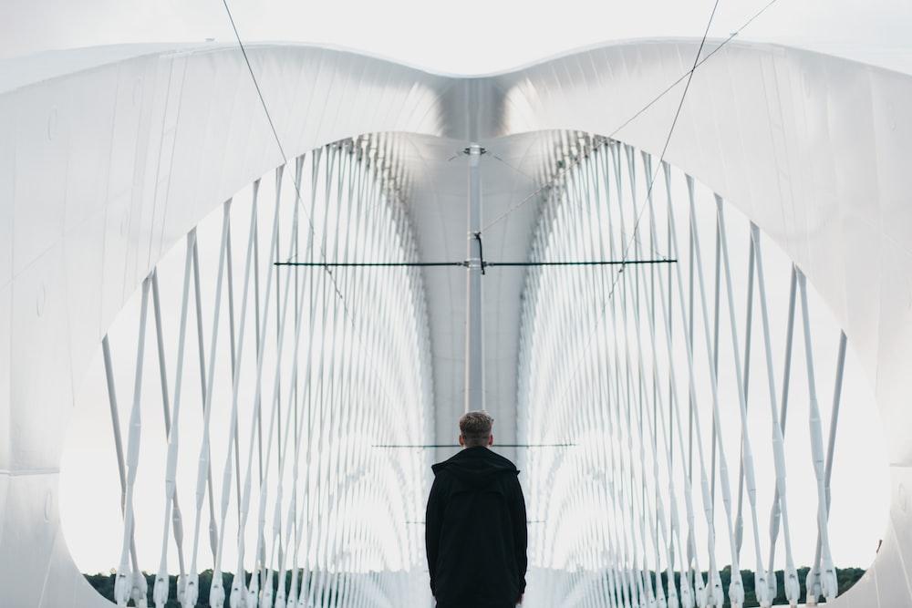 man in black suit standing on bridge