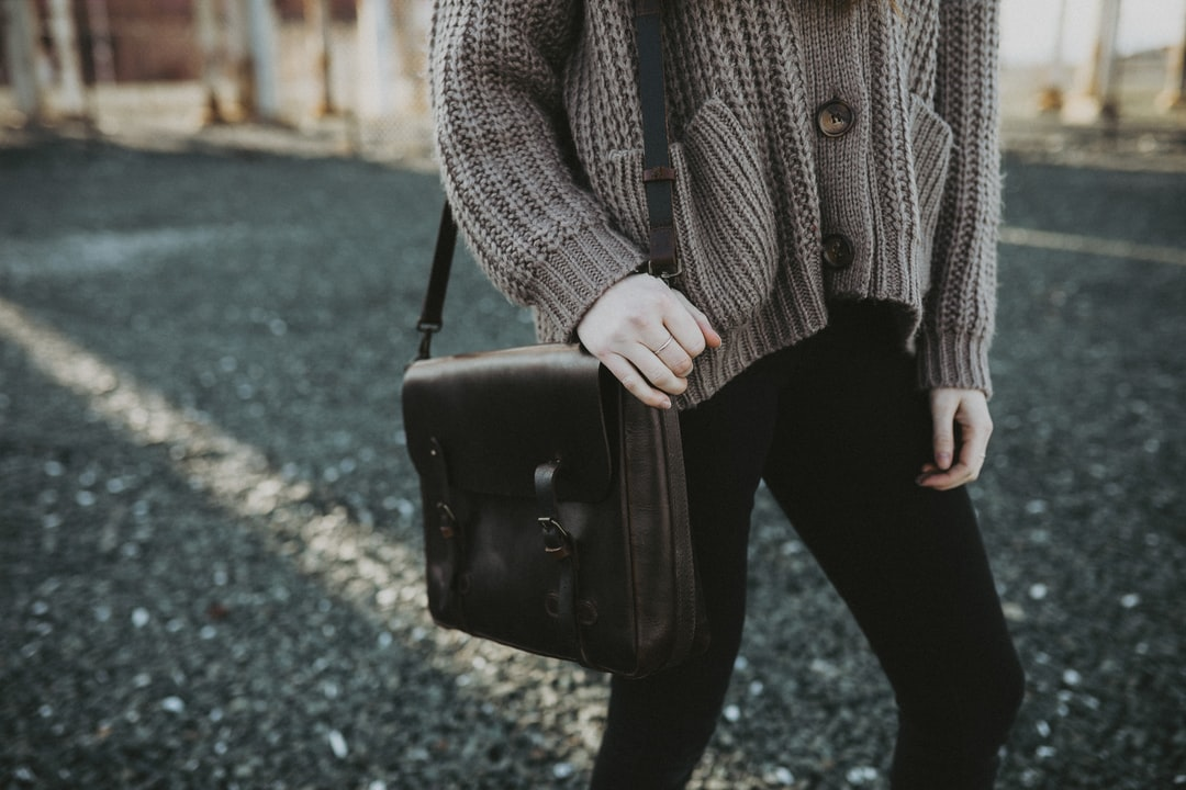 Woman In Gray Sweater and Black Pants Holding Black Leather Sling Bag - unsplash