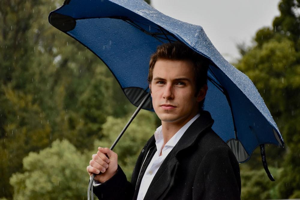 woman in black blazer holding umbrella