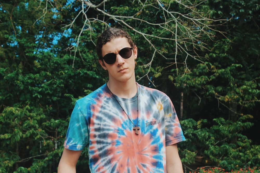 man in blue and white tie dye crew neck t-shirt wearing black sunglasses