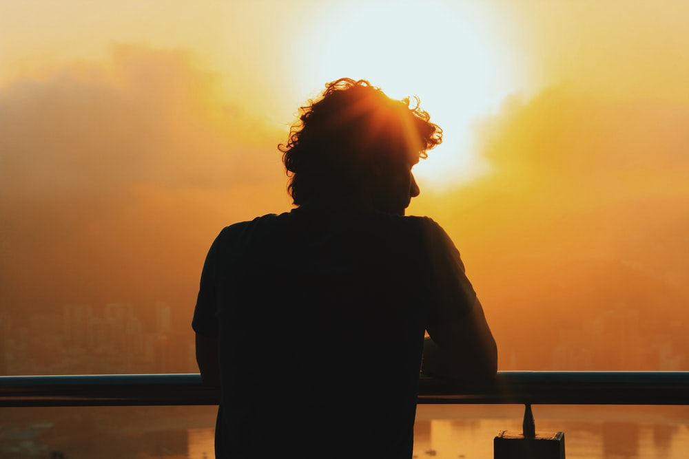 silhouette of woman standing near railings during sunset