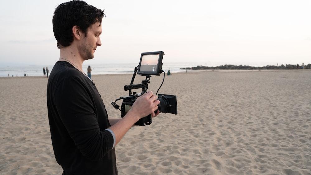 man in black t-shirt holding black camera on beach during daytime