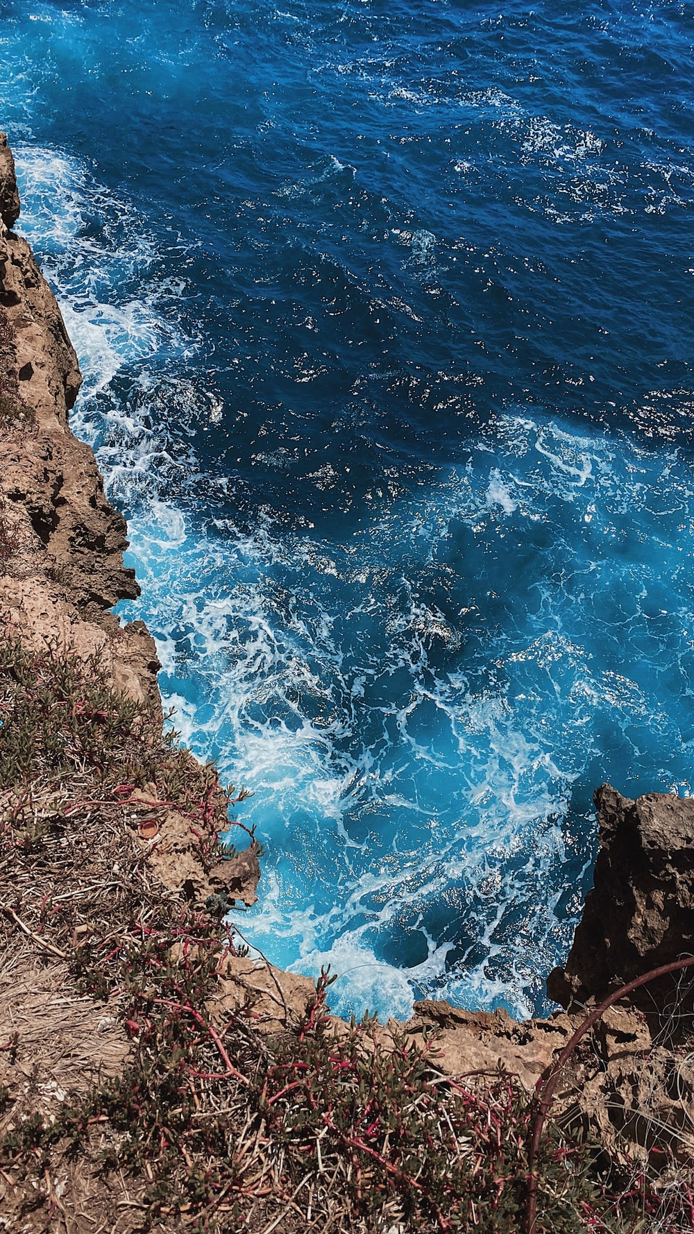 blue sea waves on brown rocky shore during daytime