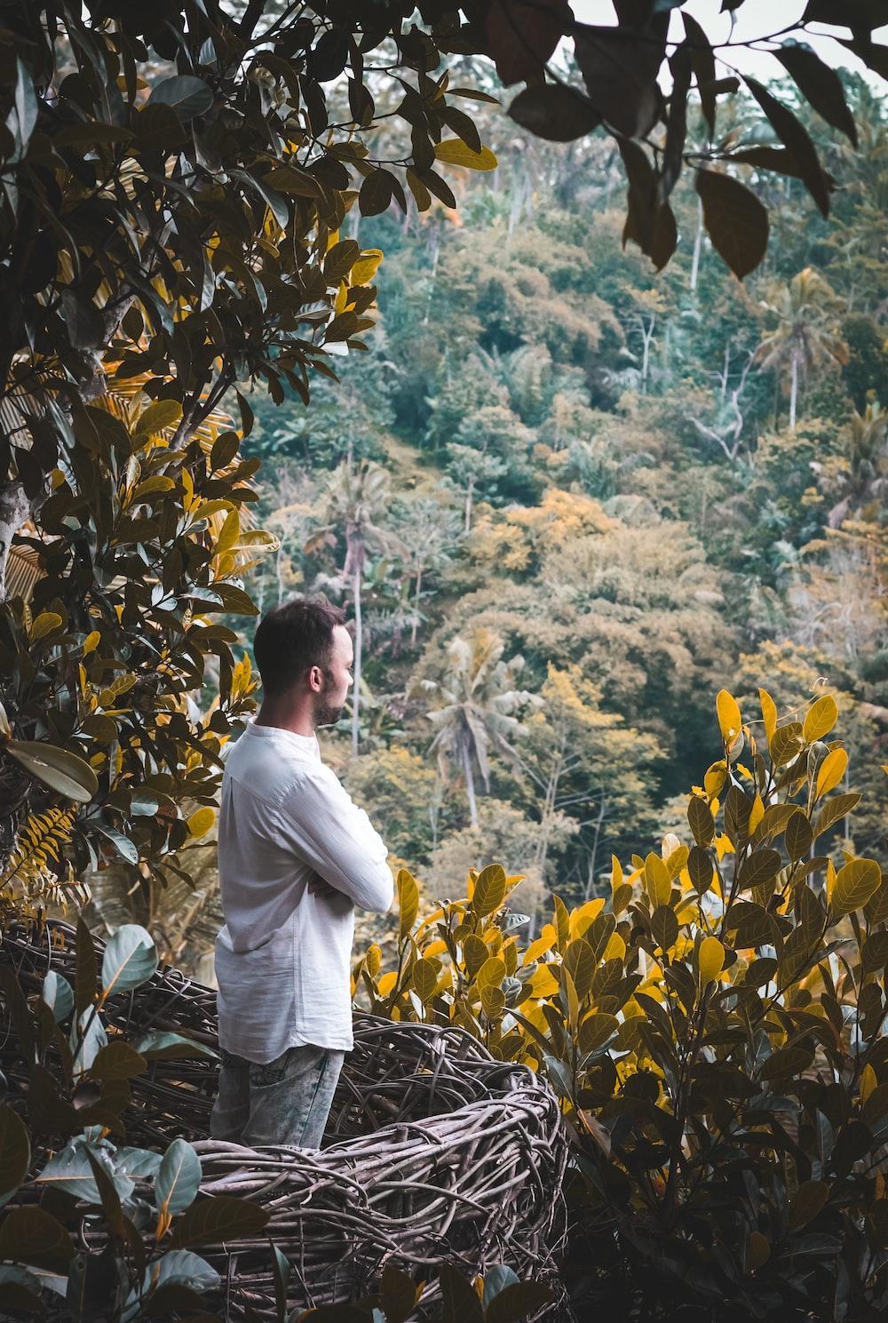 man in white dress shirt standing near green trees during daytime