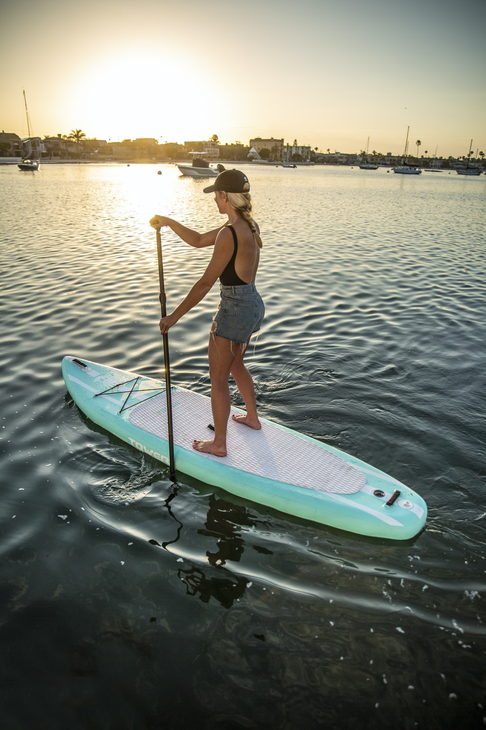 woman in blue and white shorts riding on white and green surfboard during daytime