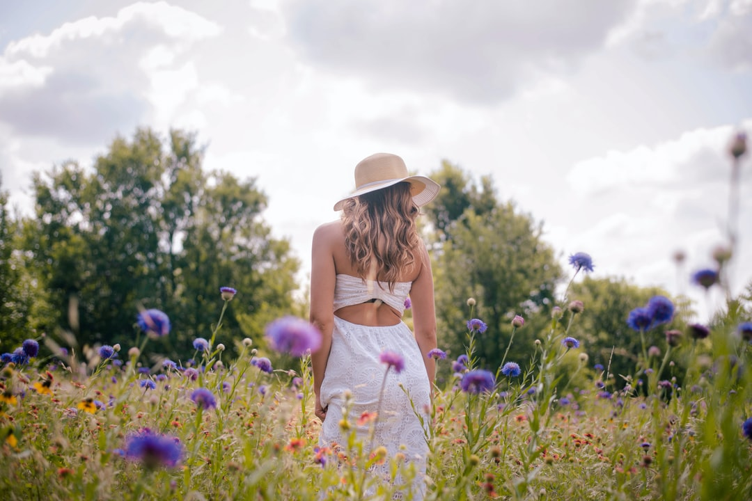 Woman In White Dress Standing On Green Grass Field During Daytime - unsplash