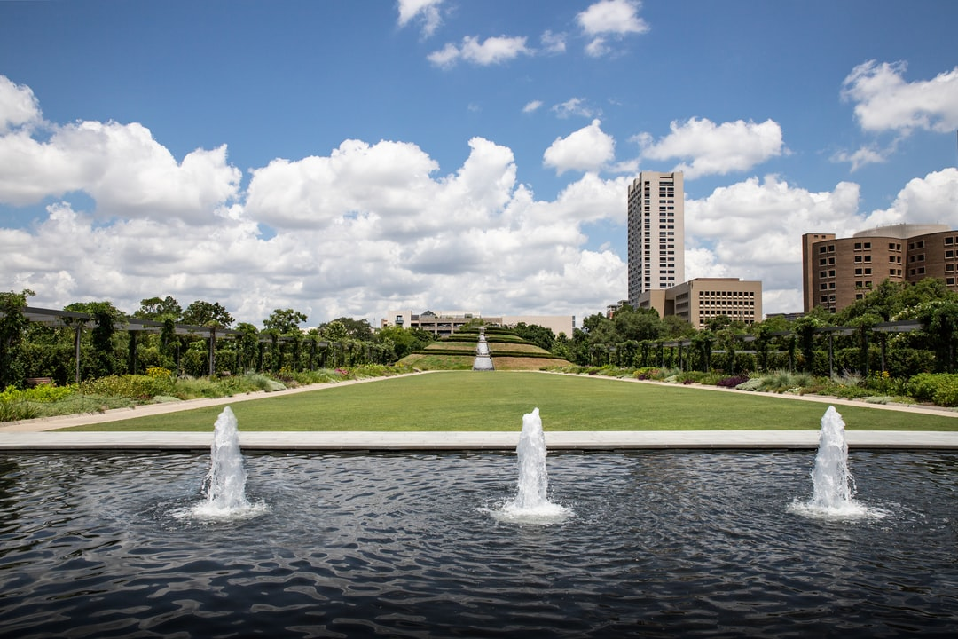 Outside Water fountain with green grass field in urban city park