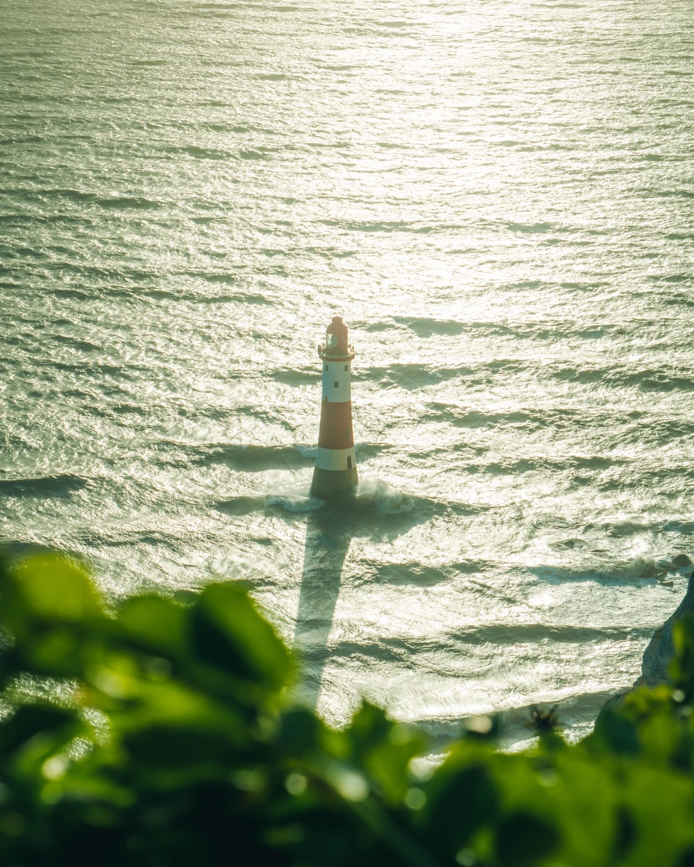 white and brown lighthouse near body of water during daytime