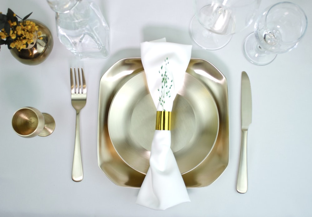 stainless steel fork and bread knife on white ceramic plate