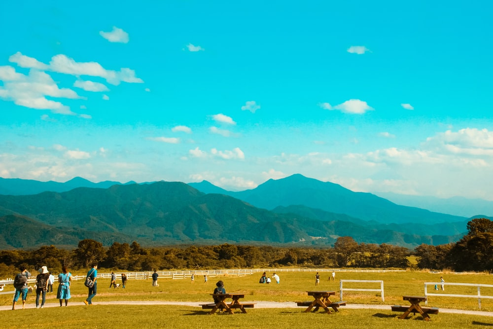 people on brown field near mountains during daytime