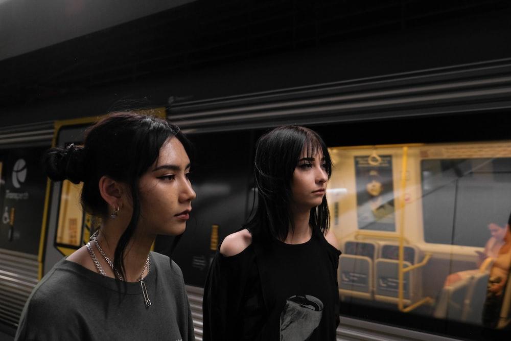 woman in black crew neck shirt standing beside yellow bus