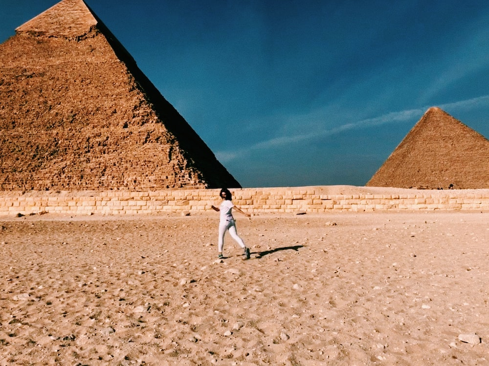 man in white shirt and gray pants walking on brown sand during daytime