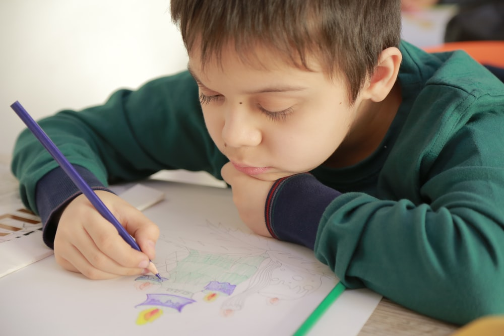 boy in green long sleeve shirt writing on white paper