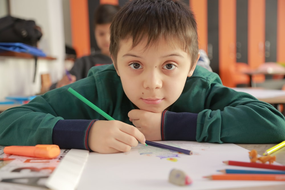 boy in green hoodie holding pencil