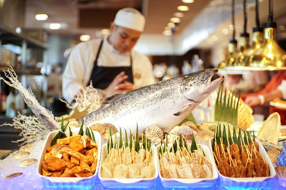 man in white apron holding fish