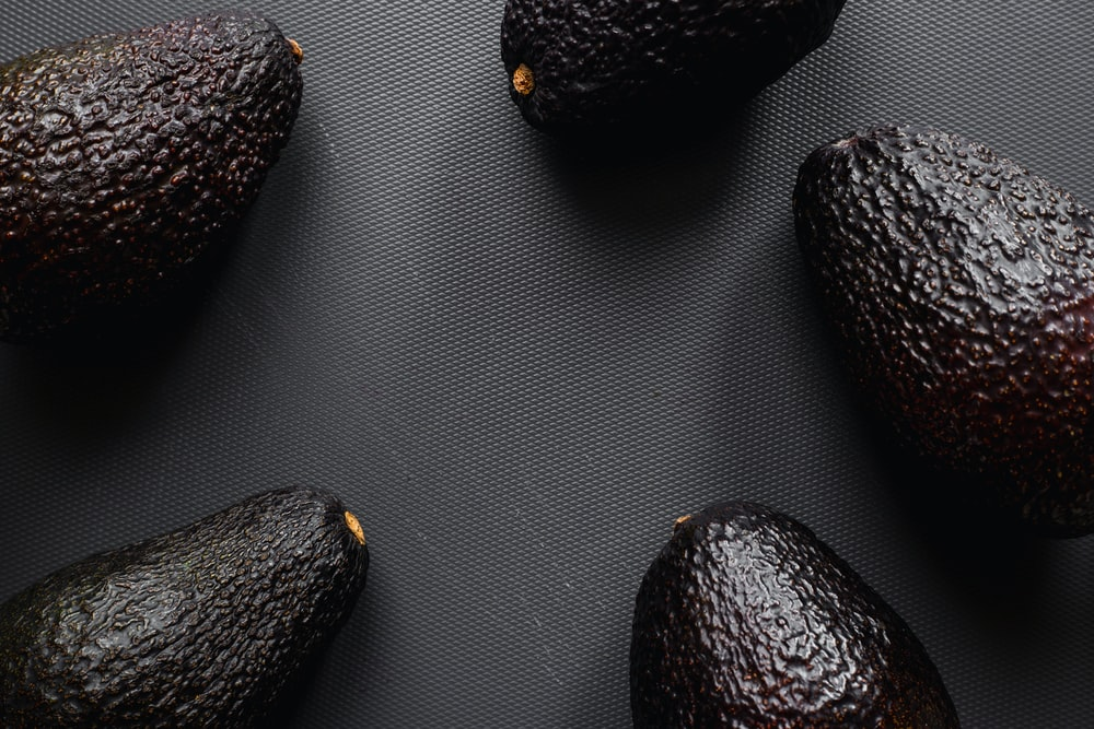 four black and brown fruits, avocado
