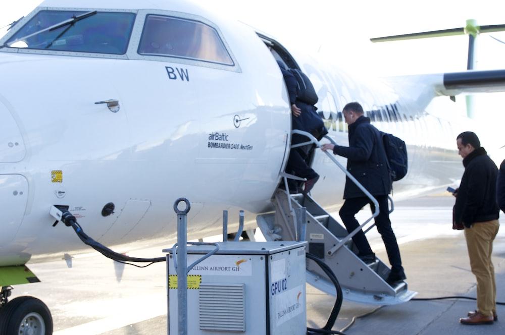 man in black jacket standing beside white airplane